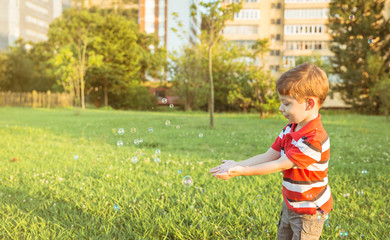 Happy boy playing with soap bubbles in the park