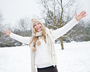 Frau lacht im Winter mit ausgestreckten Armen