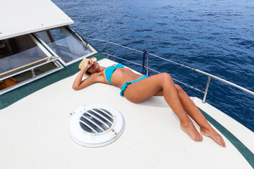 Attractive girl sunbathing on a yacht in summer