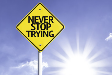Never Stop Trying road sign with sun background