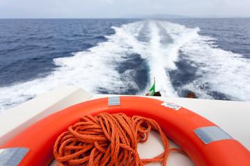 Dettaglio salvagente arancione. Barca a motore in navigazione