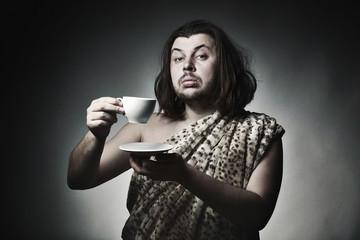 Savage man in skin of beast drink tea or coffee