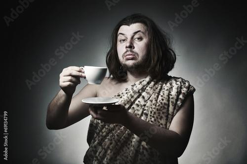 Leinwanddruck Bild Savage man in skin of beast drink tea or coffee