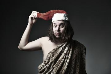 Wild man in leopard skin wear Santa Claus hat.