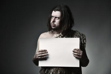 Wild man neanderthal in leopard skin hold empty paper sheet.