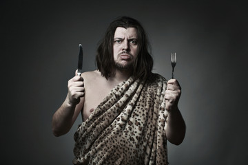Hungry wild man wearing leopard skin hold fork and knife.