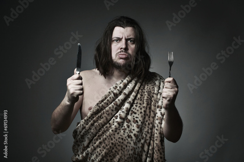 Poster Hungry wild man wearing leopard skin hold fork and knife.