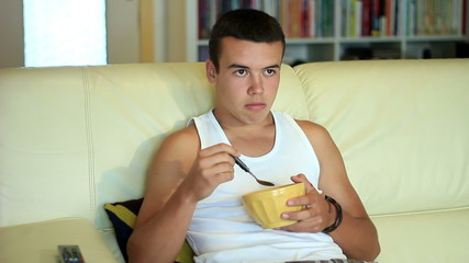 teenager boy eating cornflakes breakfast on sofa