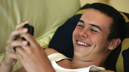 Young teenager boy on sofa watch to smartphone and laugh