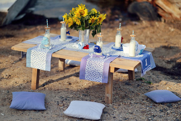 Outdoor wooden table with a bottle of milk and a vase with sunfl
