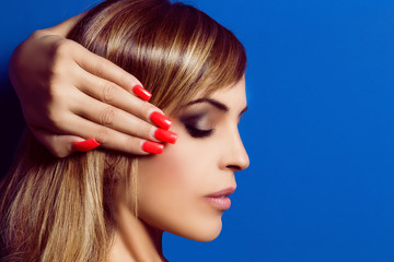 Beautiful woman with long bright hair and red nails. Glam make-u