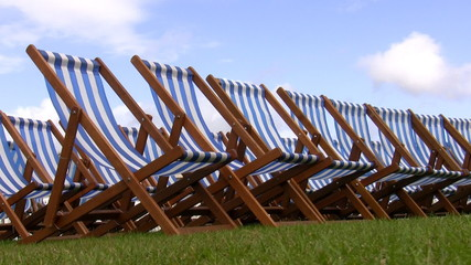 Empty striped folding chairs on the grass