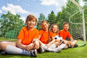 Happy children sitting together on field grass