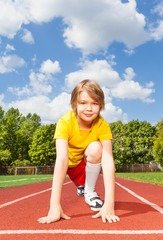 Boy in ready to run with both arms on ground
