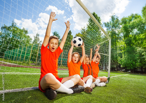Excited kids sit in row with football and arms up - 69137721