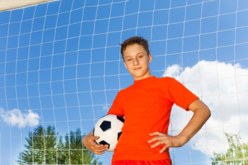 Happy boy in orange T-shirt with football