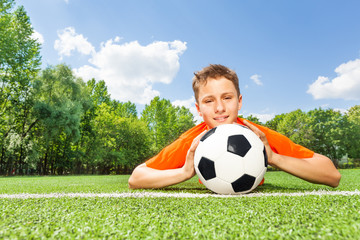 Happy boy holding football lays on green grass