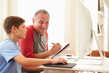 Grandson Teaching Grandfather To Use Computer