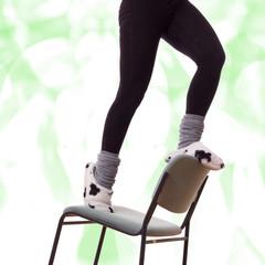 Frauenfüße in Hausschuhen klettern auf den Stuhl