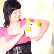 erfolgreich Sparen - Frau streichelt ihr Sparschwein