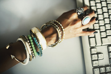 Hand typing on keyboard with bracelets and rings