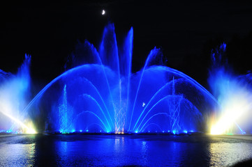 amazing dancing fountain in night illuminated blue colors