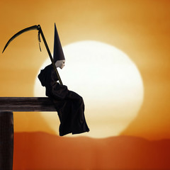 Sad person in black cloak and dunce hat with a scythe at sunset