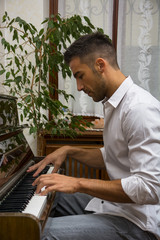 Young handsome male artist playing piano