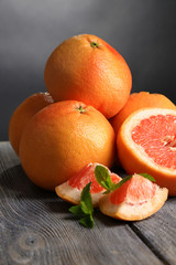 Ripe grapefruits on wooden board, on dark color background