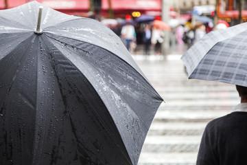 mit Regenschirm am Fußgängerüberweg