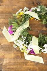 Wildflower wreath on wooden background