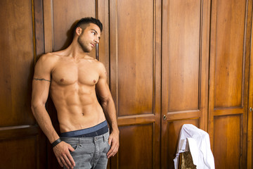 Sexy handsome young man standing shirtless