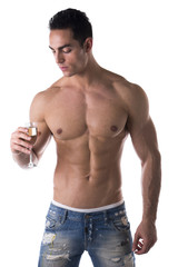 Romantic muscular shirtless young man looking at champagne flute