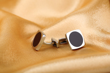 Pair of cuff links on light silk fabric background