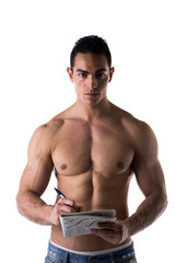 Shirtless muscular young man solving crosswords puzzles