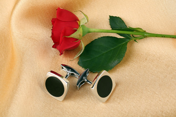 Pair of cuff links with red rose on light silk fabric