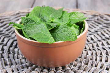 Brown round bowl of fresh mint leaves on a stand on wooden