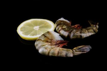 Fresh tasty prawns with lemon and dill on black background