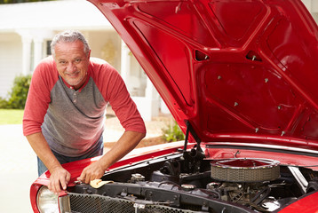Retired Senior Man Working On Restored Classic Car