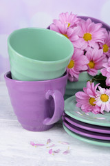 Bright dishes with flowers on table on bright background
