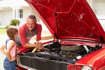Grandfather And Granddaughter Work On Restored Classic Car