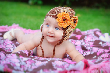 Charming child. Little girl with hat lying on her stomach