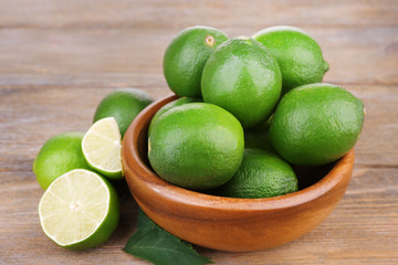 Fresh juicy limes in bowl on old wooden table