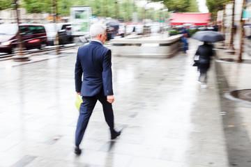 Geschäftsmann in Bewegungsunschärfe geht in der Stadt