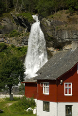 steindalsfossen, rotes holzhaus und wasserfall in norwegen