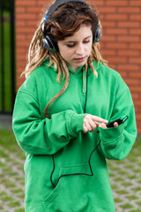Girl in headphones listening to music on mobile phone
