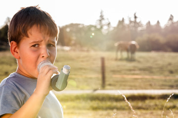 Boy using inhaler for asthma in village with cows and sunset