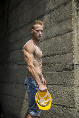 Handsome, muscular young construction worker shirtless outdoor