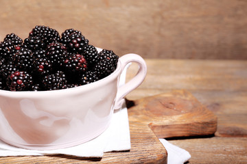 Sweet blackberries in color bowl on  wooden background