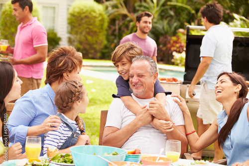 Multi Generation Family Enjoying Meal In Garden Together - 69143140